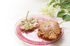 Gebraden elderflower pannekoeken met suikerglazuursuiker op een roze glasschotel stock afbeeldingen