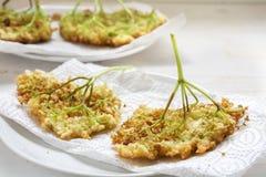 Gebraden elderflower pannekoeken, traditioneel de zomergebakje op een document stock foto's