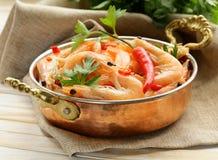 Gebraden garnalen met Spaanse pepers in een koperpan Stock Foto's