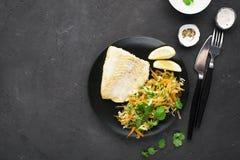 Gebraden kabeljauw met salade van verse wortelen, kool, komkommer en dille Hoogste mening horizontaal stock foto