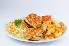 Gebraden kippenborst met gebraden gerechten en salade stock afbeelding