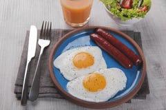 Gebraden kippeneieren met worstenontbijt op een plaat met salade Royalty-vrije Stock Afbeeldingen