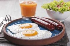 Gebraden kippeneieren met worstenontbijt op een plaat met salade Royalty-vrije Stock Foto's