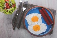Gebraden kippeneieren met worstenontbijt op een plaat met salade Stock Afbeelding