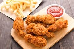 Gebraden kippentrommelstok en frieten op houten lijst Royalty-vrije Stock Foto's