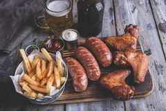 Gebraden kippenvleugels, geroosterde worsten, frieten, noten, witte en rode saus voedsel aan bier stock afbeelding