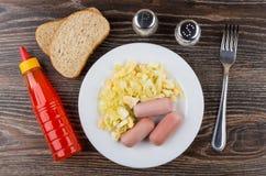 Gebraden kool met worsten in plaat, fles ketchup, brood Stock Fotografie