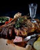 Gebraden lapje vlees met aromatische kruiden en groenten, uitstekend mes, vork en glas op een donkere achtergrond Stock Fotografie
