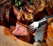 Gebraden lapje vlees met aromatische kruiden en groenten, uitstekende mes en vork op een houten achtergrond Royalty-vrije Stock Foto