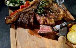 Gebraden lapje vlees met aromatische kruiden, groenten in het zuur, saus, uitstekende mes en vork op een houten achtergrond Royalty-vrije Stock Afbeeldingen