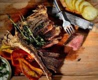 Gebraden lapje vlees met aromatische kruiden, groenten in het zuur, saus, uitstekende mes en vork op een houten achtergrond, hoog Stock Foto's