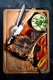 Gebraden lapje vlees met aromatische kruiden, peper, saus, uitstekende mes en vork op een houten achtergrond, hoogste mening Stock Foto's
