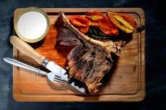 Gebraden lapje vlees met aromatische kruiden, peper, uitstekende mes en vork op een houten achtergrond, hoogste mening Royalty-vrije Stock Afbeeldingen