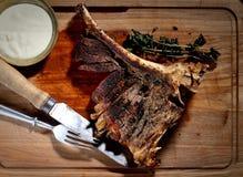 Gebraden lapje vlees met aromatische kruiden, saus, uitstekende mes en vork op een houten achtergrond Stock Fotografie