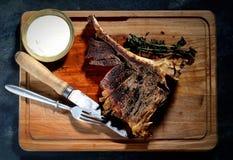 Gebraden lapje vlees met aromatische kruiden, saus, uitstekende mes en vork op een houten achtergrond, hoogste mening Stock Foto's