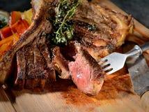 Gebraden lapje vlees met aromatische kruiden, uitstekend vork en mes op een houten achtergrond Royalty-vrije Stock Foto