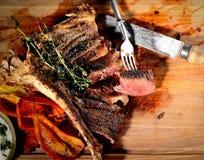 Gebraden lapje vlees met aromatische kruiden, uitstekend vork en mes op een houten achtergrond Royalty-vrije Stock Afbeelding