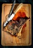Gebraden lapje vlees met aromatische kruiden, uitstekende mes en vork op een houten achtergrond Royalty-vrije Stock Foto's
