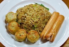 Gebraden rijst in zwarte sojasaus en varkensvleesworst met kip jock op schotel stock fotografie