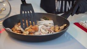 Gebraden ringen van pijlinktvis met kruiden en ui in de pan stock video
