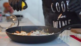 Gebraden ringen van pijlinktvis met kruiden en ui in de pan stock videobeelden