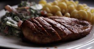 Gebraden sappig lapje vlees, Italiaanse deegwaren met plantaardige salade op een witte plaat stock footage