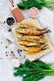 Gebraden spiering op een houten Hakbord, een dille, een roze zout, een peper en een knoflook Grijze achtergrond, hoogste mening,  stock foto