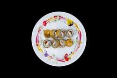 Gebraden sushi met een komkommer, één of andere roomkaas, tobikokaviaar, zalm en paling Hoogste mening Geïsoleerd op een zwarte a Royalty-vrije Stock Fotografie
