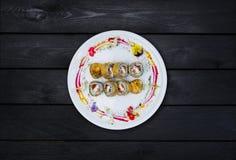 Gebraden sushi met een komkommer, één of andere roomkaas, tobikokaviaar, zalm en paling Hoogste mening Zwarte houten achtergrond Royalty-vrije Stock Fotografie