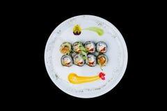 Gebraden sushi met een komkommer, sommige roomkaas, tobikokaviaar en garnalen Hoogste mening Geïsoleerd op een zwarte achtergrond Stock Afbeeldingen