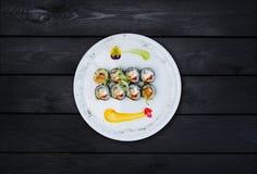 Gebraden sushi met een komkommer, sommige roomkaas, tobikokaviaar en garnalen Hoogste mening Zwarte houten achtergrond Stock Afbeelding