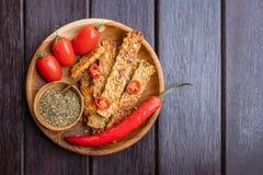 Gebraden tempeh, Spaanse peperpeper, verse kersentomaten en mengeling van droge kruiden in houten pot met houten lepel op een ron Royalty-vrije Stock Afbeelding