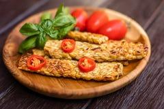 Gebraden tempeh verfraaid met Spaanse peperpeper, verse kersentomaten en basilicumbladeren op een rond houten dienblad over donke Royalty-vrije Stock Foto's