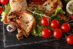 Gebraden varkenskotelet op een zwarte plaat met kruiden, kruiden en tomaten stock foto's