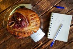 Gebraden varkensvleesbeen in een transparante plaat op de keukenschaal Tellende calorie?n, prote?nen, vetten en koolhydraten in v stock foto
