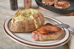 Gebraden varkensvleeskotelet met een aardappel in de schil stock afbeeldingen