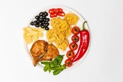 Gebraden varkensvleesribben met spaghetti, kersentomaten, basilicum, olijven, hete peper en kaas Stock Foto