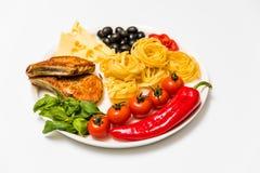 Gebraden varkensvleesribben met spaghetti, kersentomaten, basilicum, olijven, hete peper en kaas Stock Afbeelding