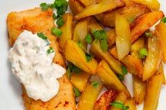 Gebraden vis met patat op een witte plaat op de keukenlijst met tartaarsausclose-up - foto, beeld royalty-vrije stock foto's