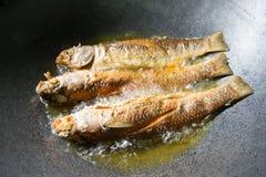 Gebraden vissen Drie vissen die in hete olie in pan of koekepan braden Stock Afbeelding