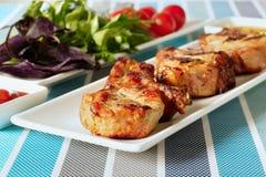 Gebraden vlees op een witte plaat en een plaat met greens royalty-vrije stock afbeelding