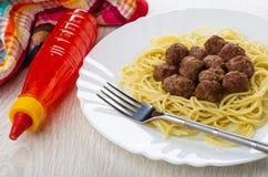 Gebraden vleesballetjes met spaghetti, vork in schotel, fles met ketchup, servet op houten lijst royalty-vrije stock foto's
