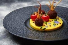 Gebraden vleesballetjes met tomaat op aardappels in een zwarte plaat Stock Afbeelding