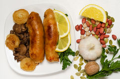 Gebraden worst met paddestoelen en uien op een witte plaat Royalty-vrije Stock Foto's