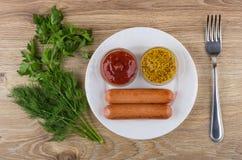 Gebraden worsten, kommen met mosterd en ketchup in plaat, greens Royalty-vrije Stock Fotografie