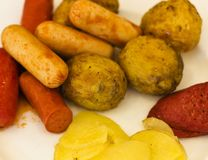 Gebraden worsten met aardappelen in de schil op een witte plaat Selectief F royalty-vrije stock afbeeldingen