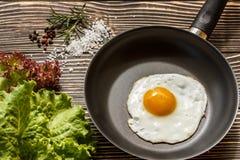 Gebraden zonnige kant op eieren op een pan op een bruine oude houten raad Royalty-vrije Stock Foto