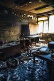 Gebrand huisbinnenland Gebrande ruimte in de industriële bouw, verkoold meubilair en beschadigde flat na brand stock fotografie