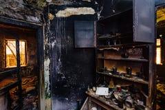 Gebrand huisbinnenland Gebrand meubilair, keukenkast, verkoold muren en plafond in zwart roet stock foto's