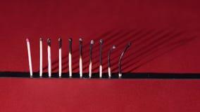 Gebrand matchsticks op rode achtergrond stock video